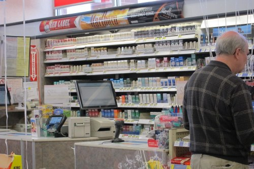 Typical Walgreens checkout counter tobacco display. Note the fire extinguisher sign on the far left, and the blu electronic cigarette display far right. Photo: Martin Pion